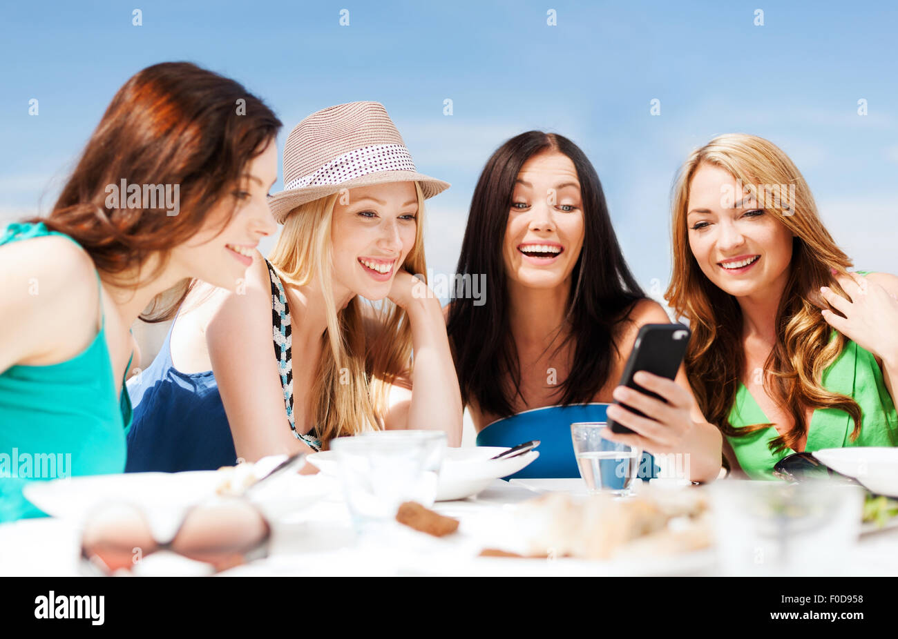 Girls Looking At Smartphone In Cafe On The Beach Stock Photo