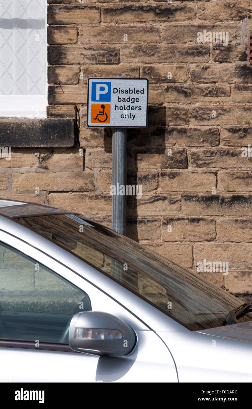 Disabled badge holders parking sign behind parked car. - Stock Image