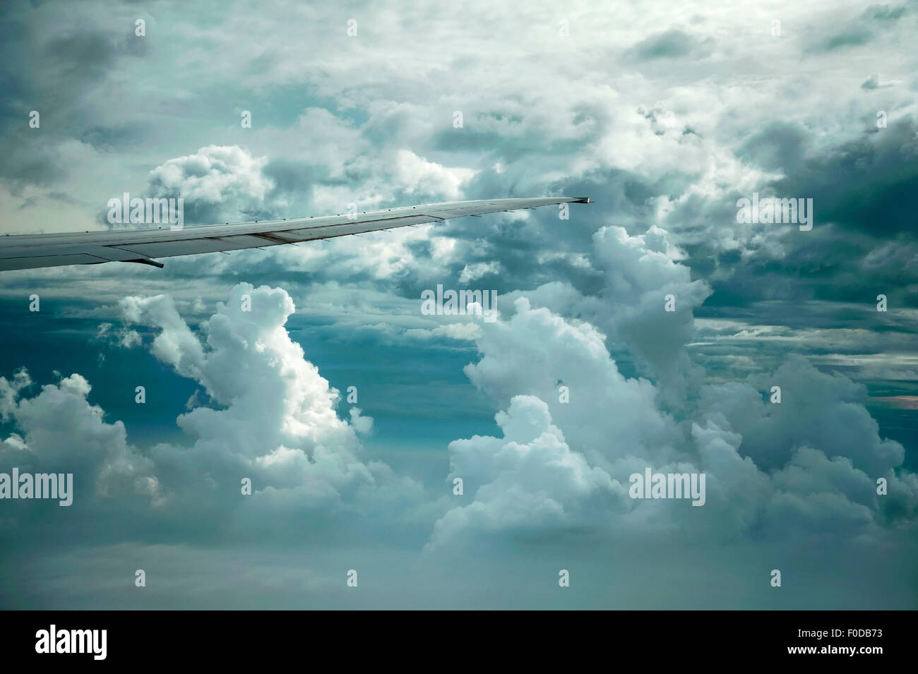 Dramatic cloud formations and the wing of a Boeing 777-300 - Stock Image