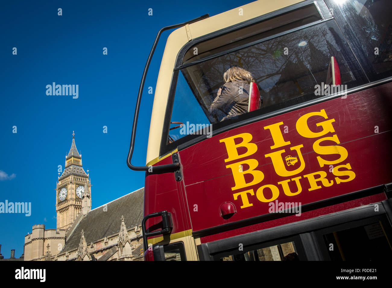 Tourists on the top deck of a sightseeing bus in London. - Stock Image