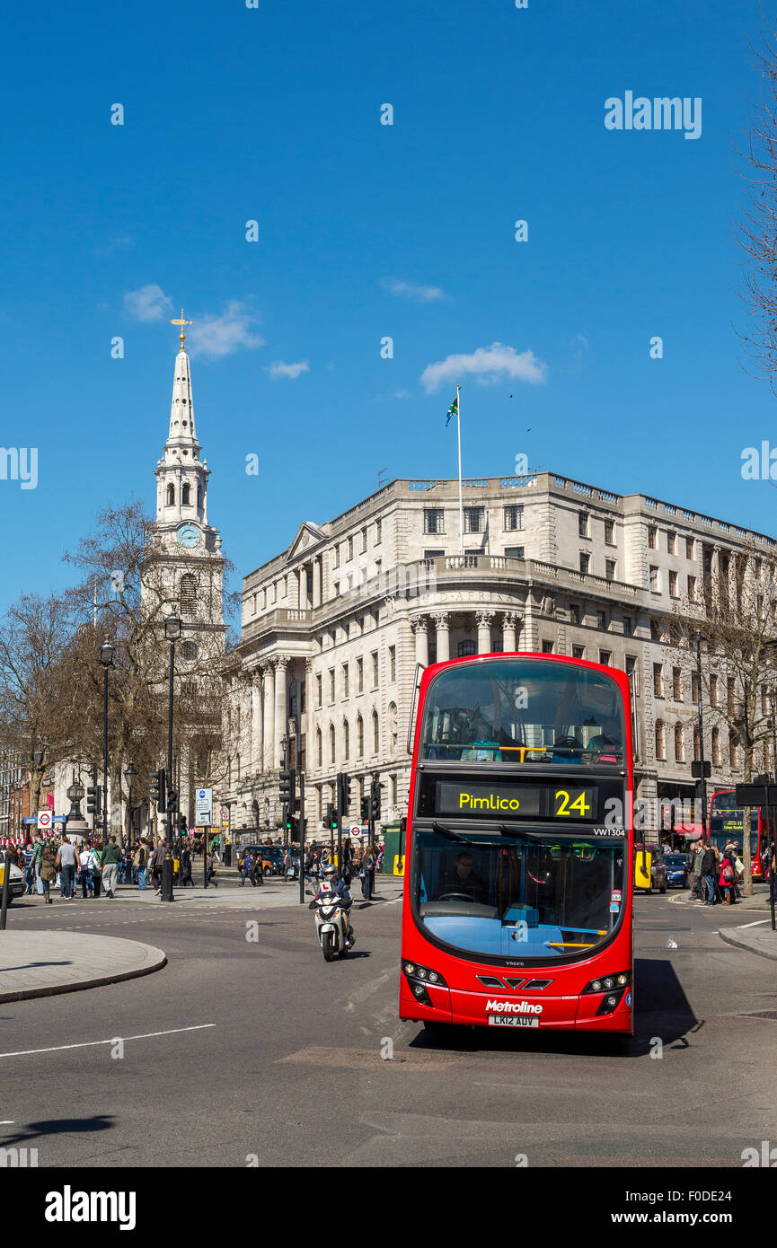 Double decker bus driving past Trafalgar Square in the City of London, England. - Stock Image