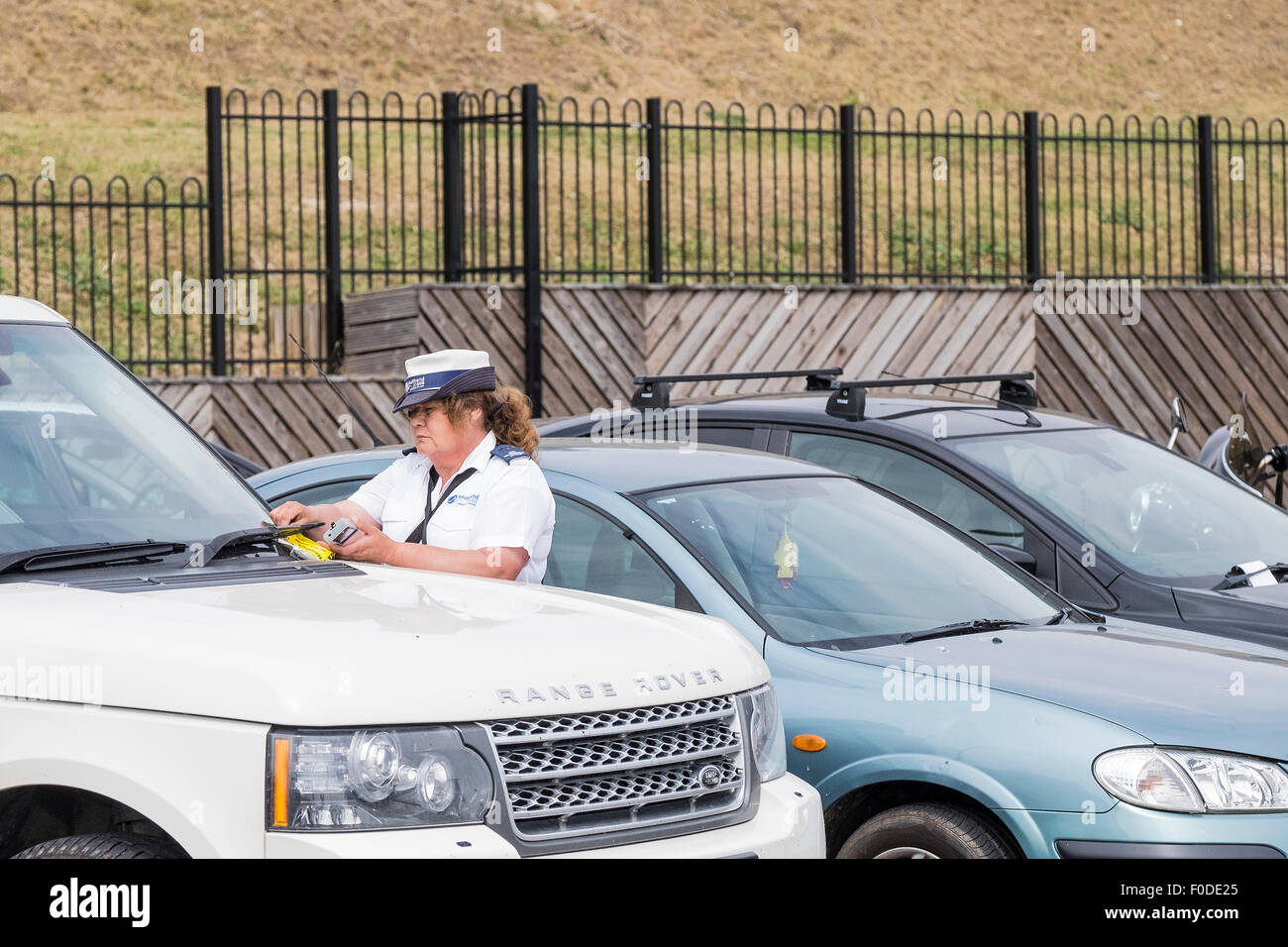 A Traffic Warden issuing a parking ticket on Southend seafront in Essex. - Stock Image