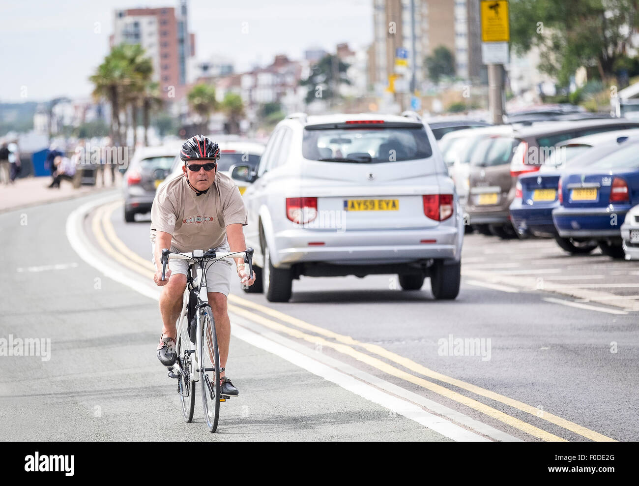 A cyclist using the cycle lane on Southend seafront in Essex. - Stock Image