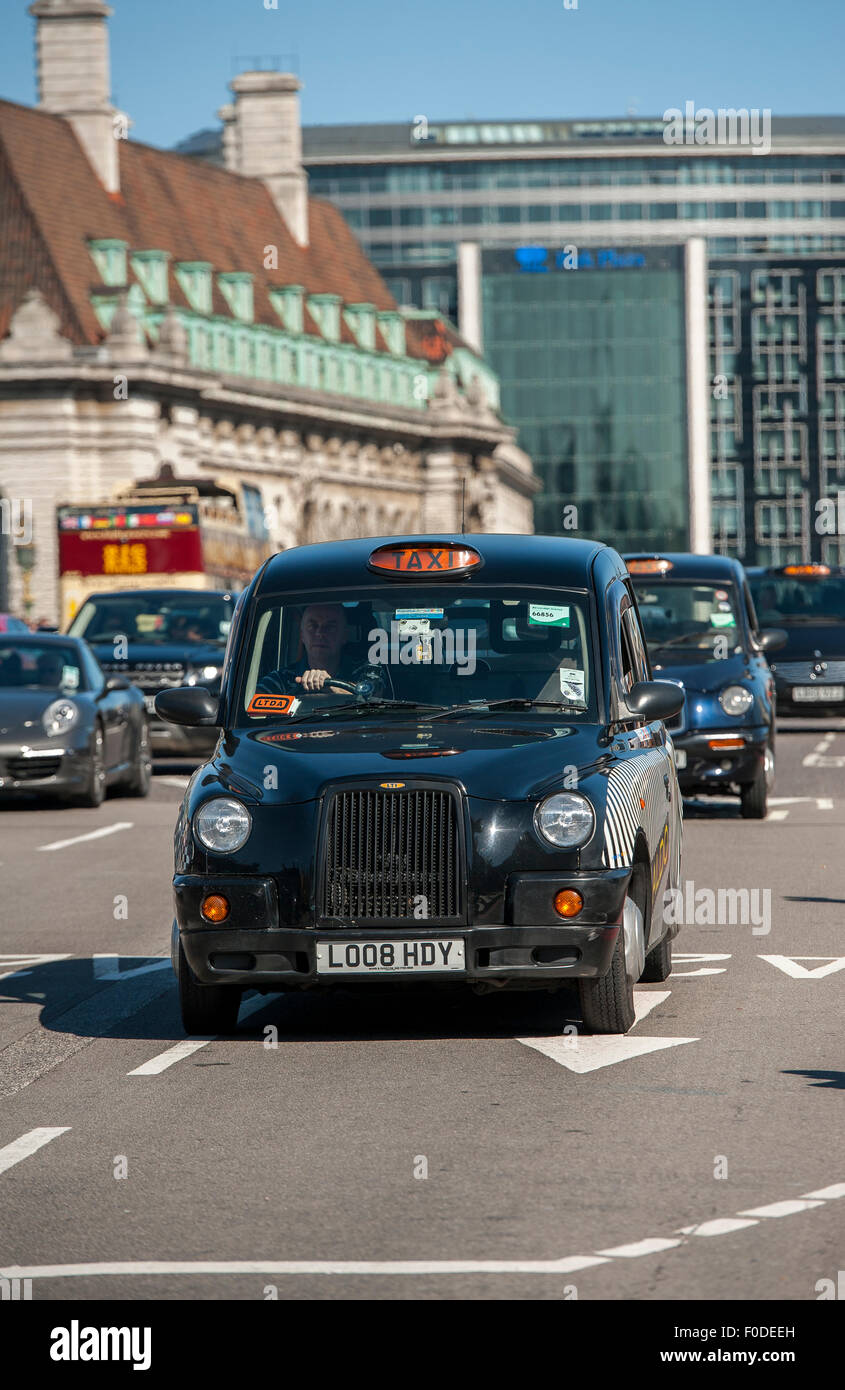 Black cab driving through the streets of the City of London, England. - Stock Image