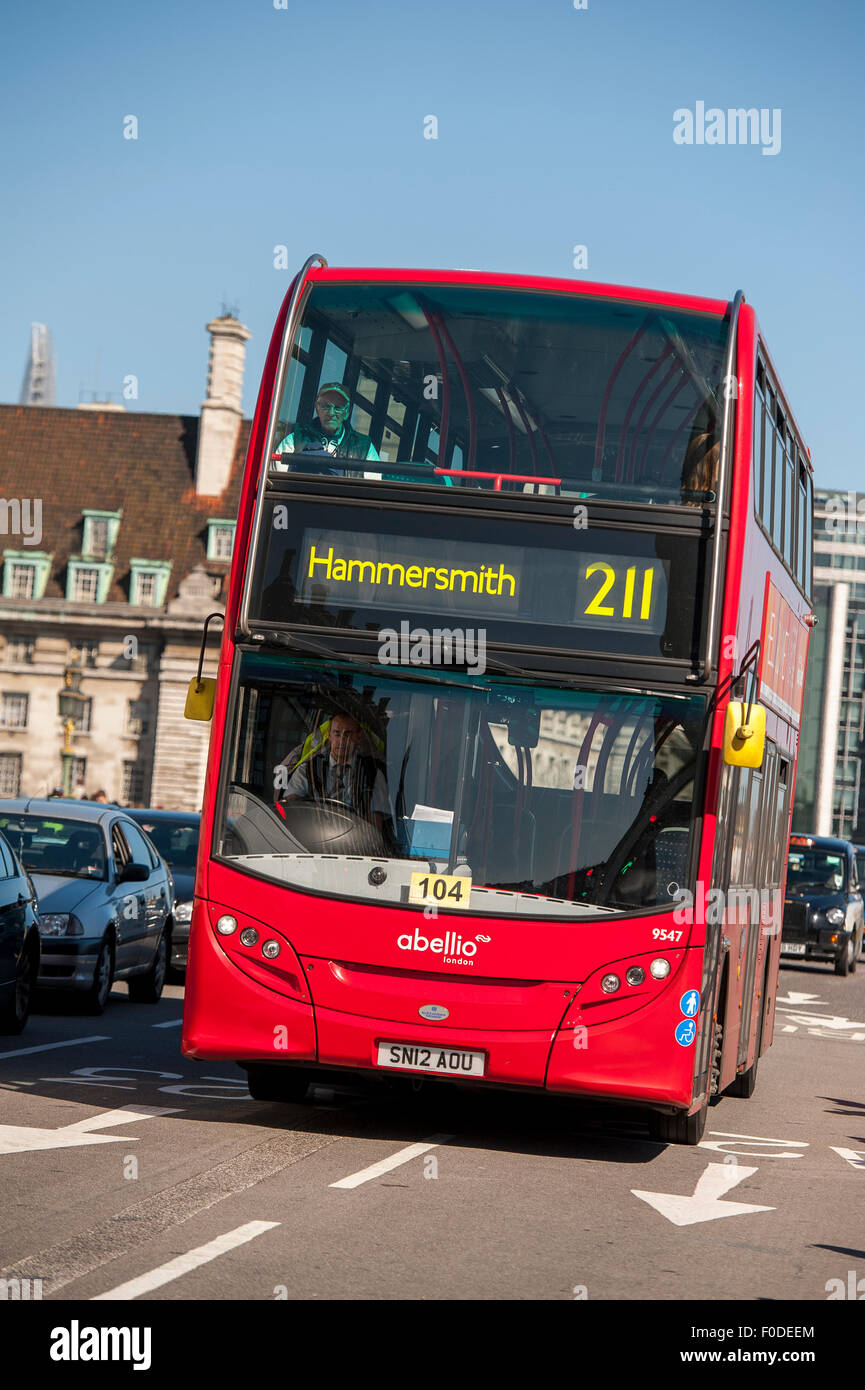 Double decker bus driving along a road in the City of London, England. - Stock Image