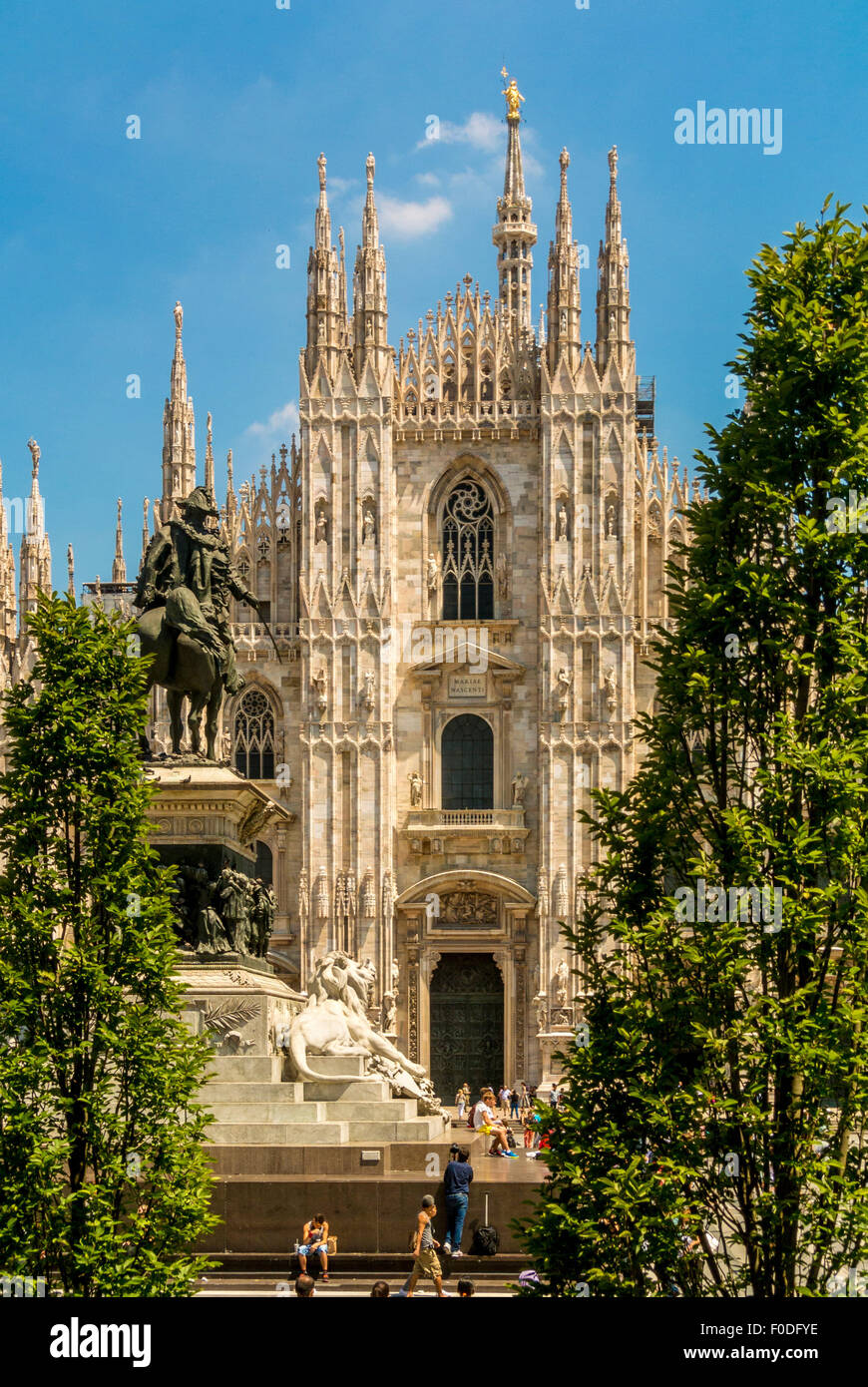 Milan Cathedral  with King Victor's statue and trees in the foreground. Milan Italy - Stock Image