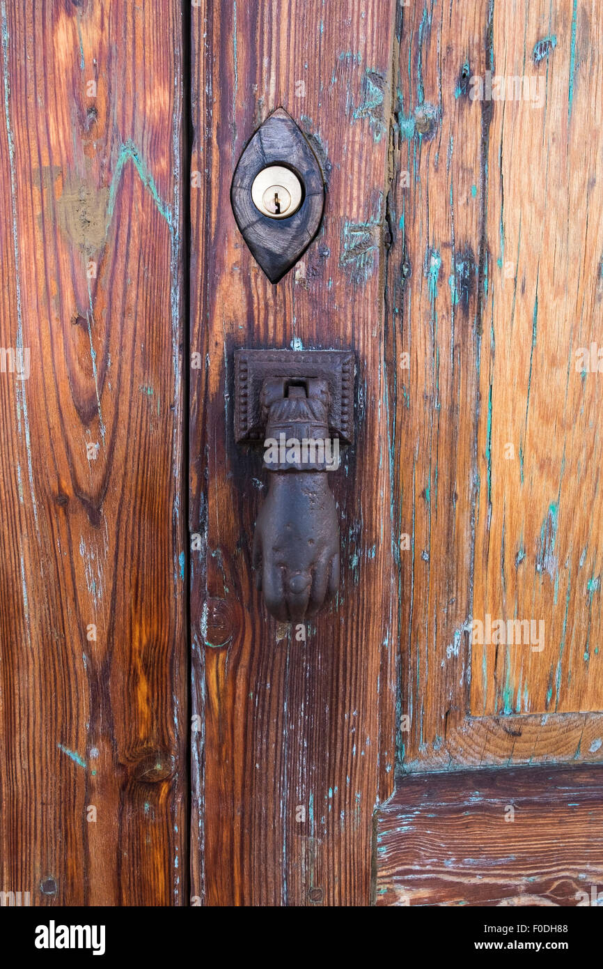 Cast iron hand door knocker and yale lock on old wooden door Stock Yale Wooden Door Locks on