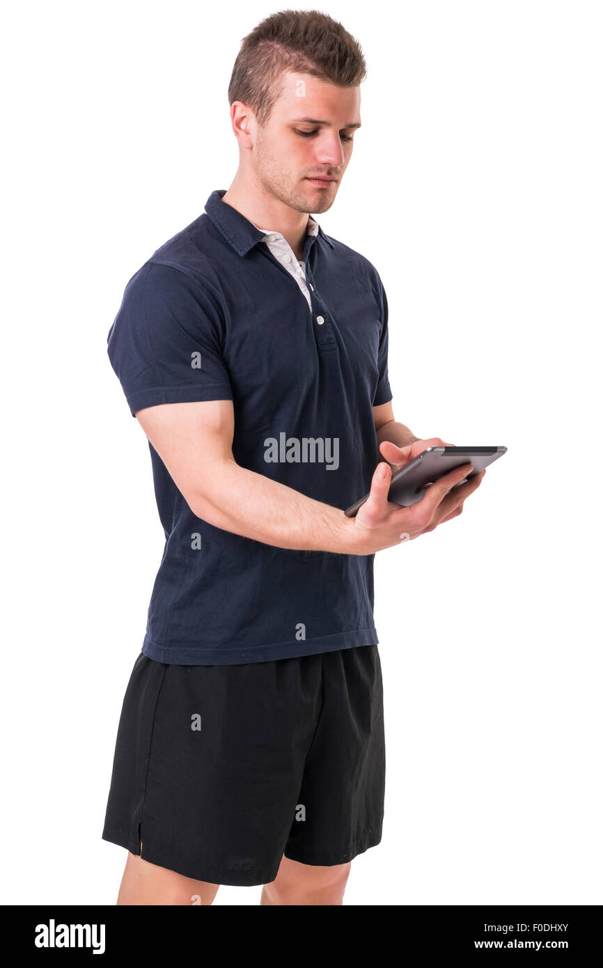 Handsome young personal trainer with tablet PC, standing isolated on white background - Stock Image
