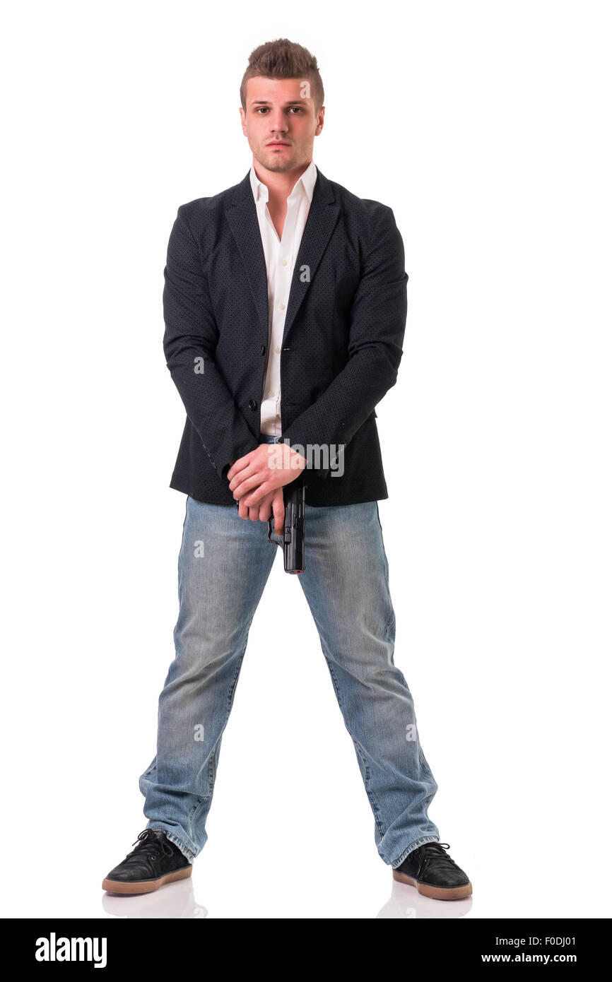 Elegant man with gun, dressed as a spy or secret agent, with earphones, isolated on white. Full figure shot - Stock Image