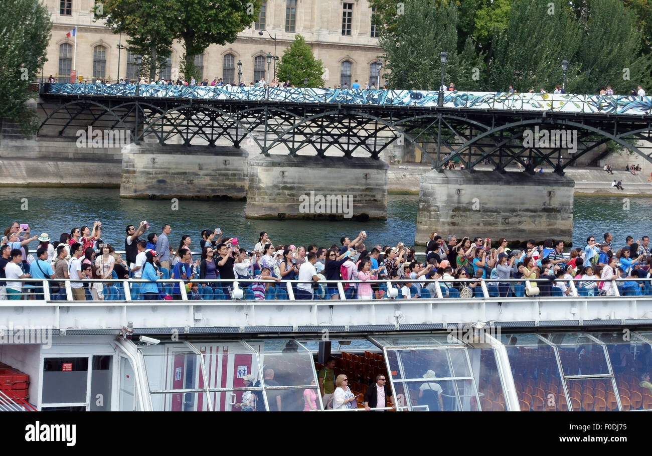 Tourists on River Seine sightseeing boat in Paris near Pont des Arts, France taking photographs - Stock Image