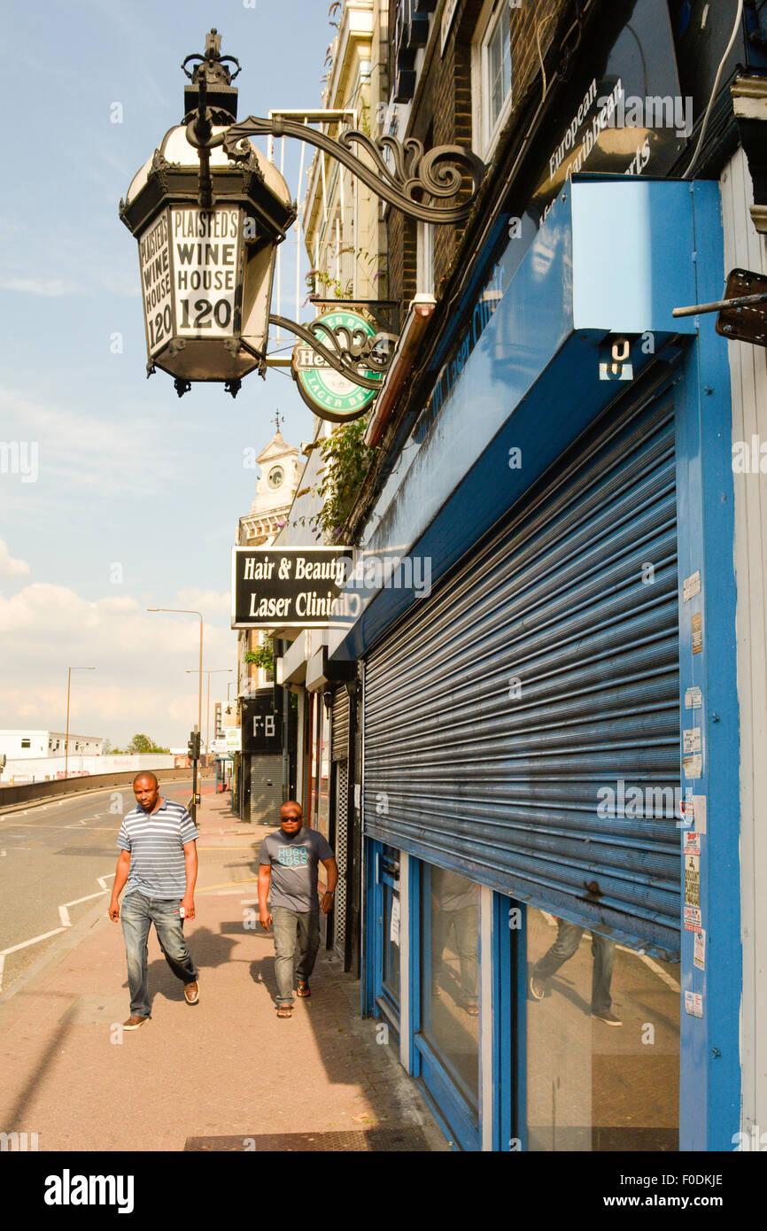 Two black men walk past run down wine bar on Woolwich Hight Street in London SE18 - Stock Image