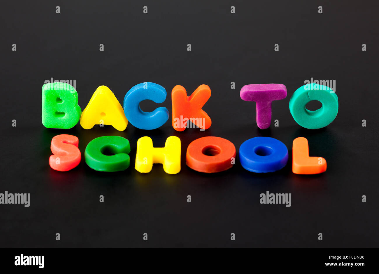 Words Back to school on black background. Letters made of child's play clay. - Stock Image