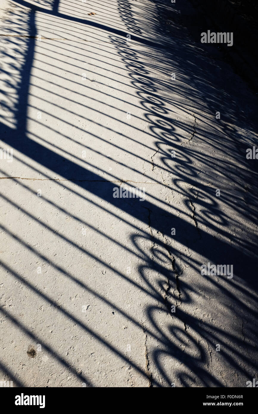 forged fence shadow on an asphalt track - Stock Image