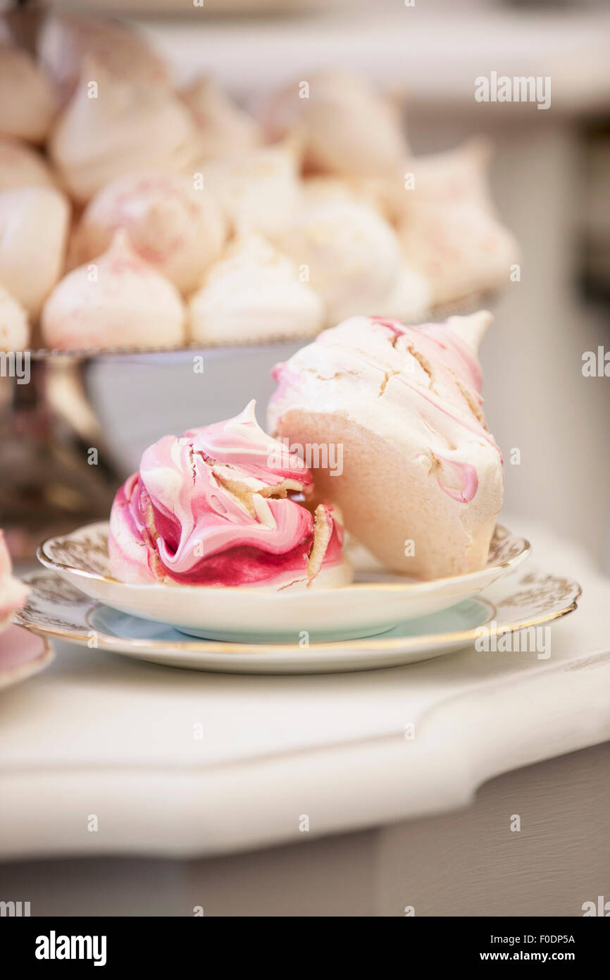 Pink and white meringues and macaroons on vintage plates - Stock Image