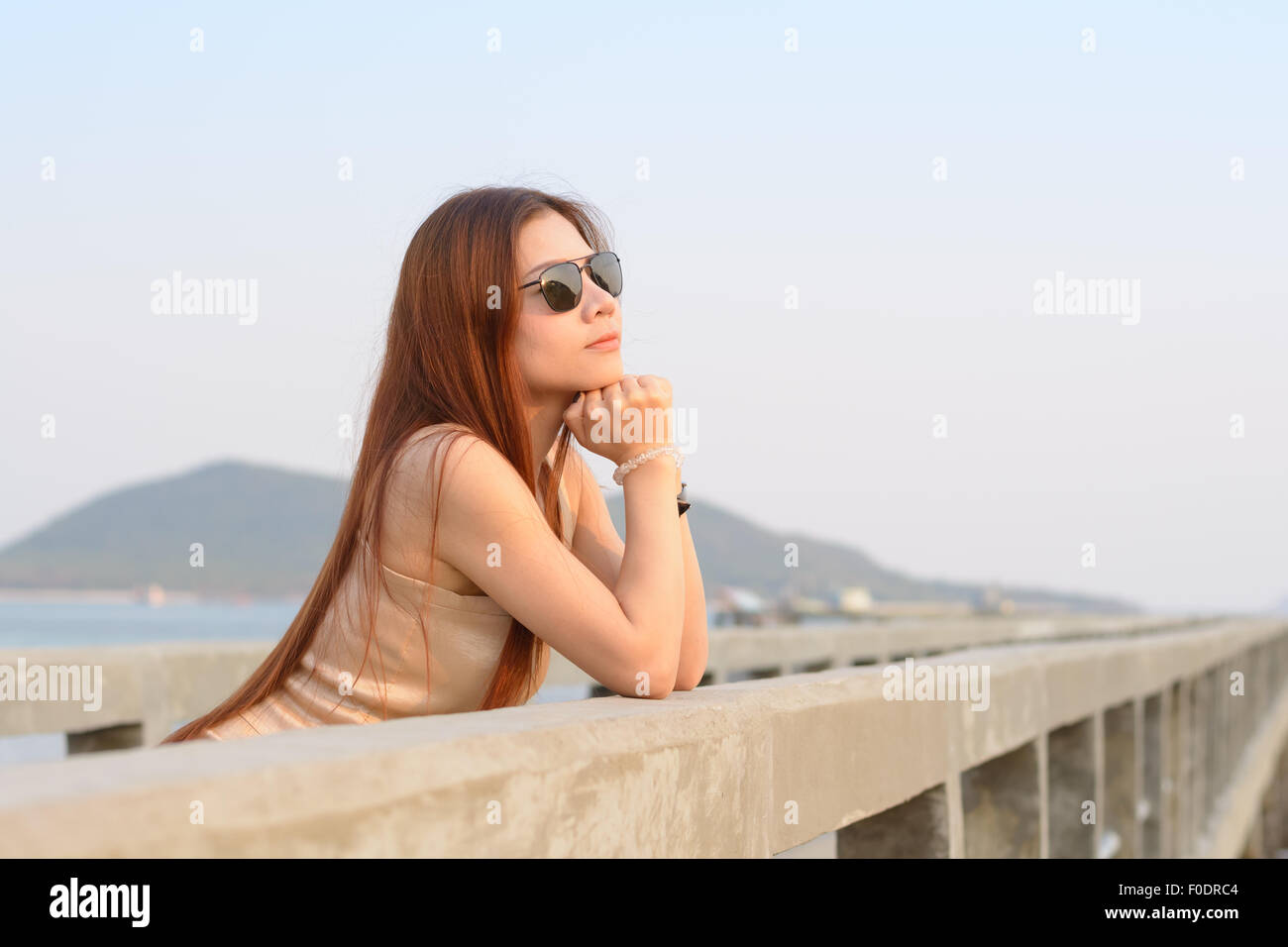Asian women wear sunglass standing on the bridge - Stock Image