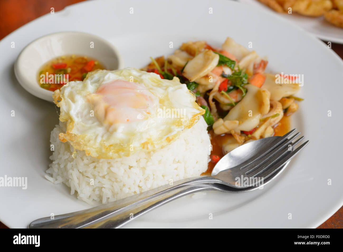 Steamed rice Fried basil leaves with mixed seafood and topped with fried egg - Stock Image