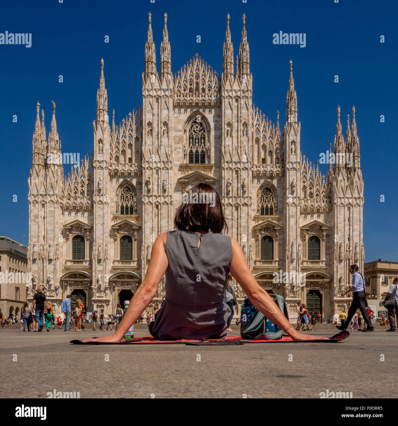 Female tourist sitting on a picnic blanket, on the ground outside Milan Cathedral. Italy - Stock Image