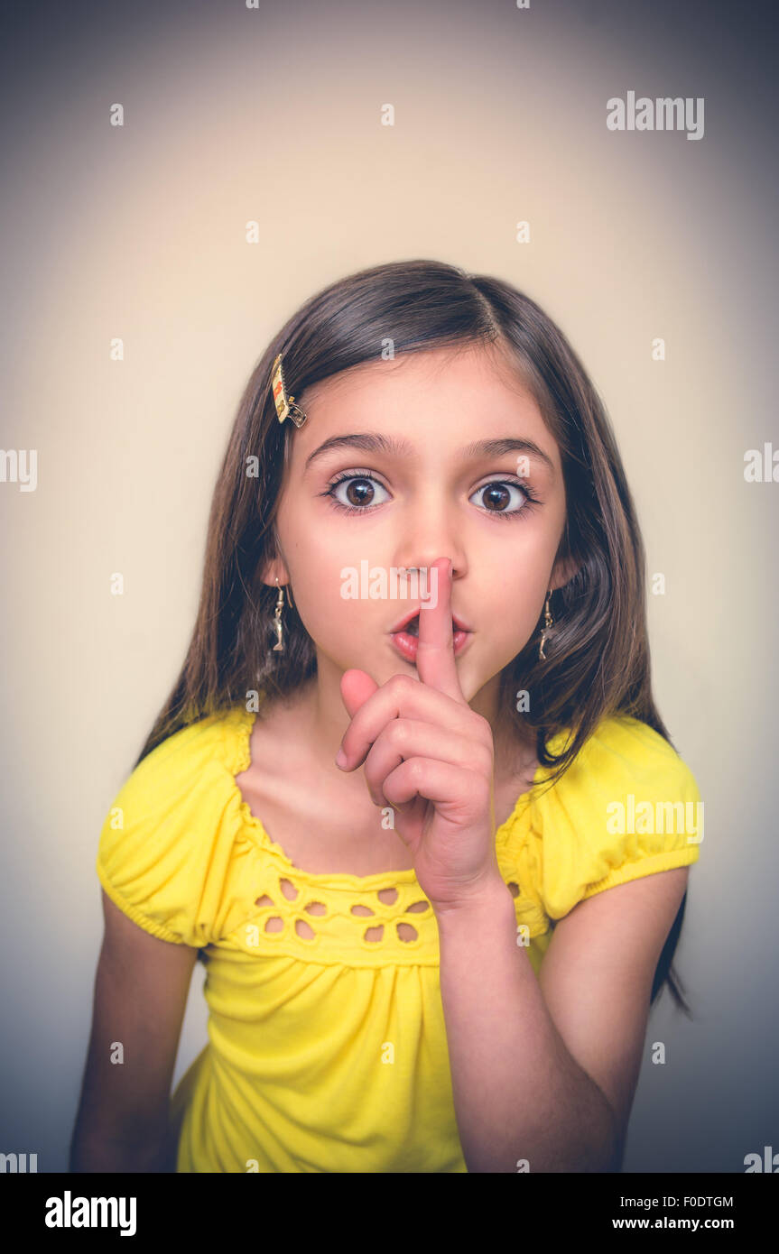 LIttle girl with fingers to lips making a gesture for quiet. - Stock Image
