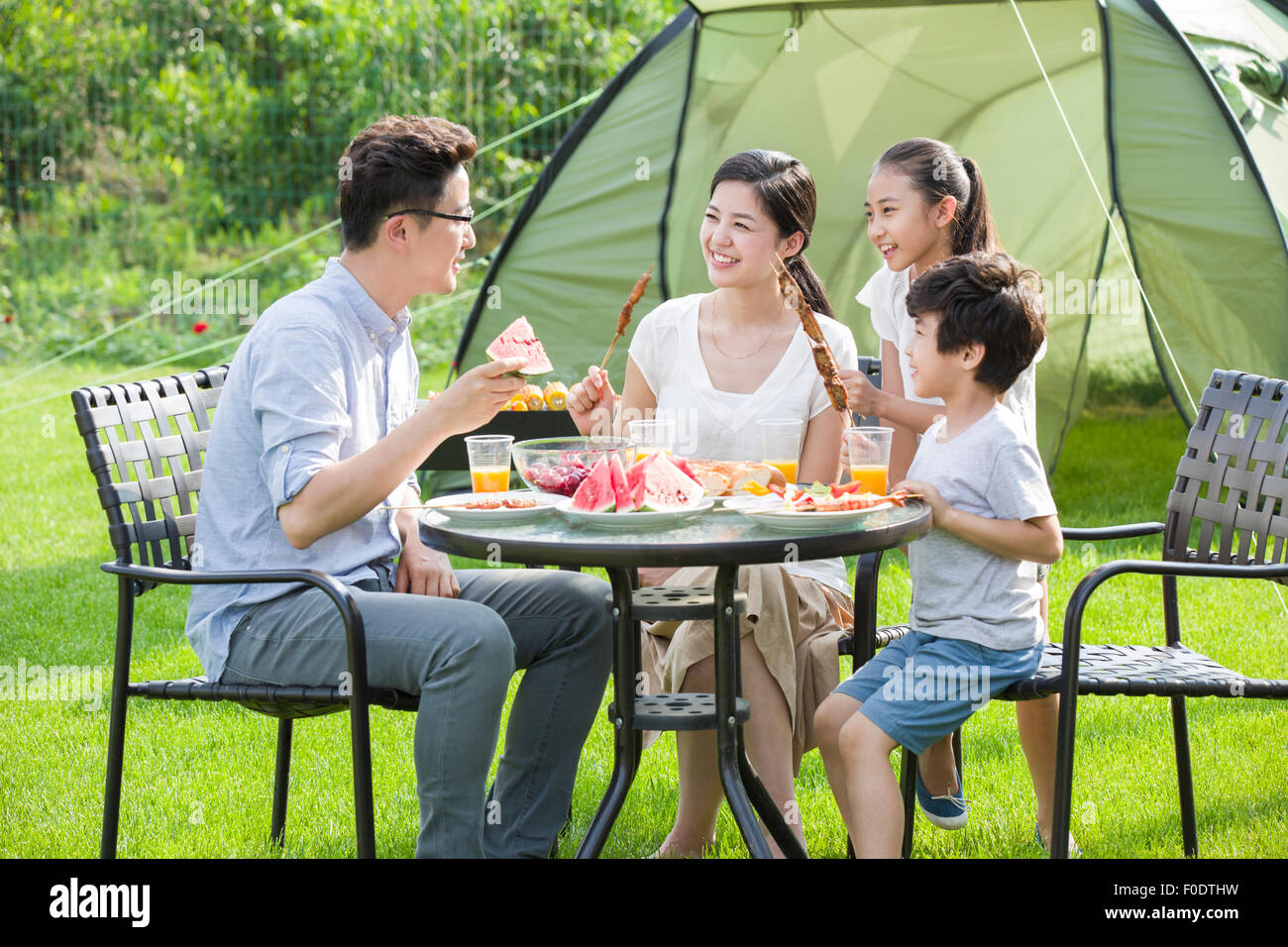 Young family picnicking outdoors - Stock Image