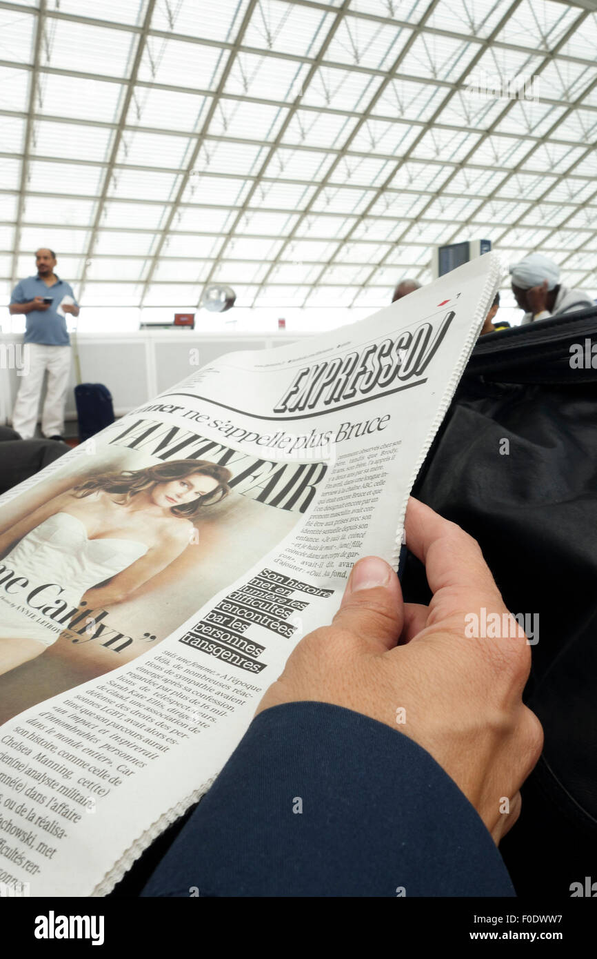 Close-up hand holding newspaper. Woman reading newspaper at gate airport, Roisy, Charles de gaulle, Paris, France. - Stock Image