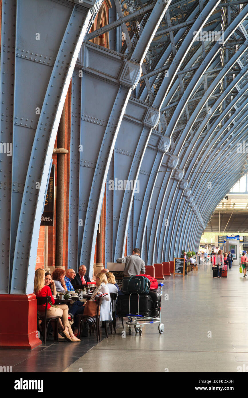 Travelers sitting under the steelwork of St Pancras Railway Station London - Stock Image