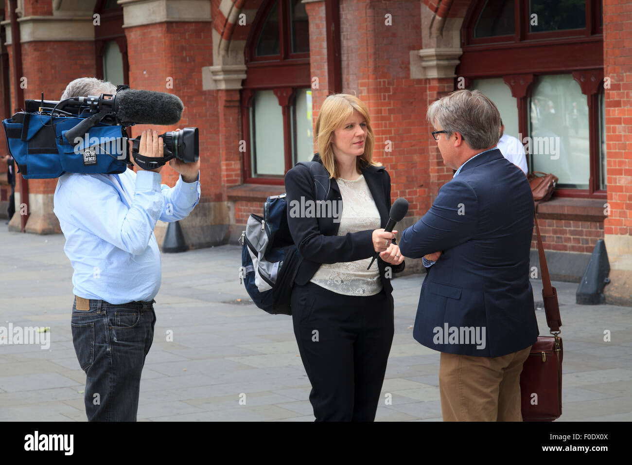 Female reporter and television camera man interview traveler at St Pancras - Stock Image