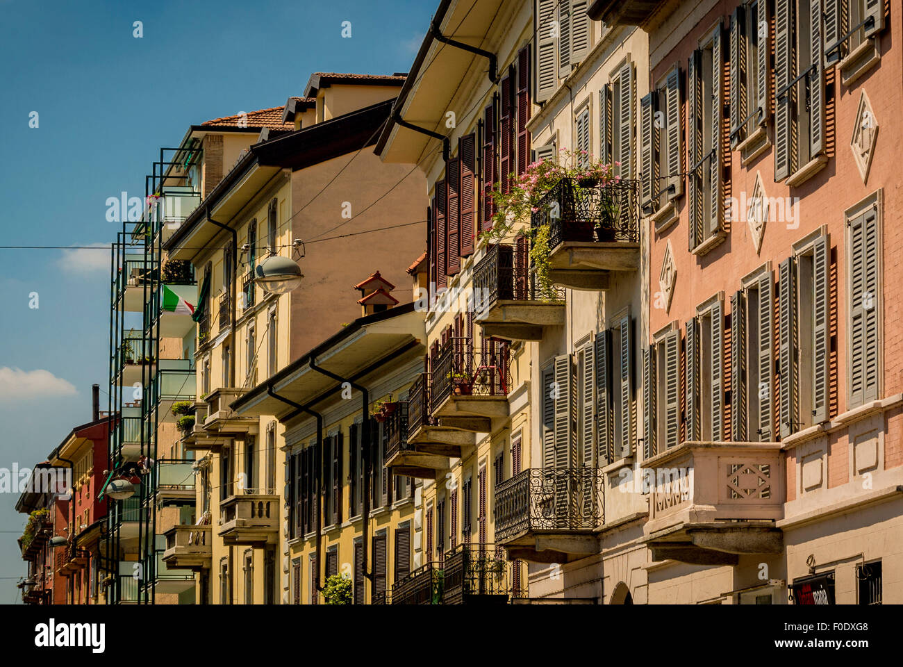 Buildings with wooden shuttered windows along the Grand Canal, Naviglio, Milan, Italy - Stock Image