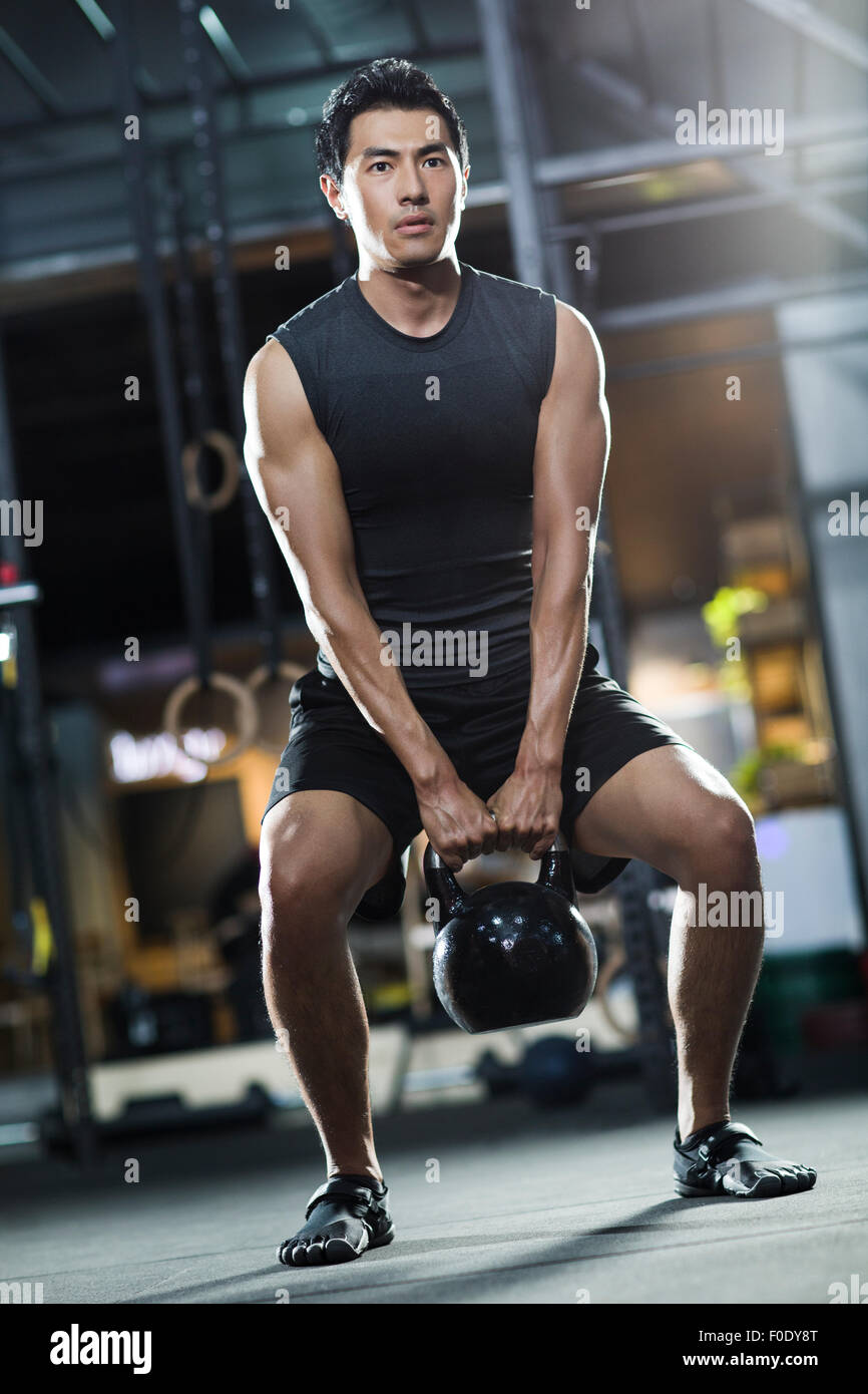 Young man training with kettlebell in crossfit gym - Stock Image