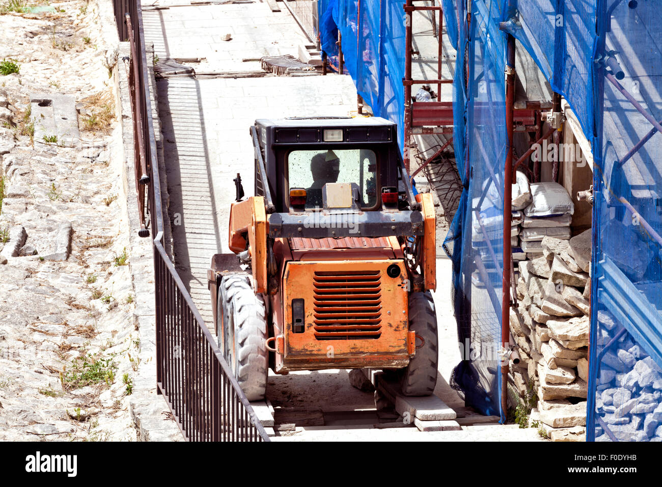Small orange lifting vehicle going uphill on a building construction site, full of cement bags, stone slabs, with - Stock Image