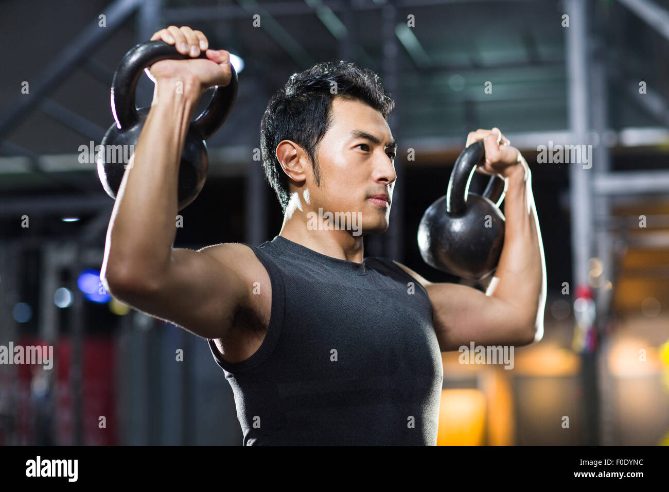 Young man training with kettlebells in crossfit gym - Stock Image