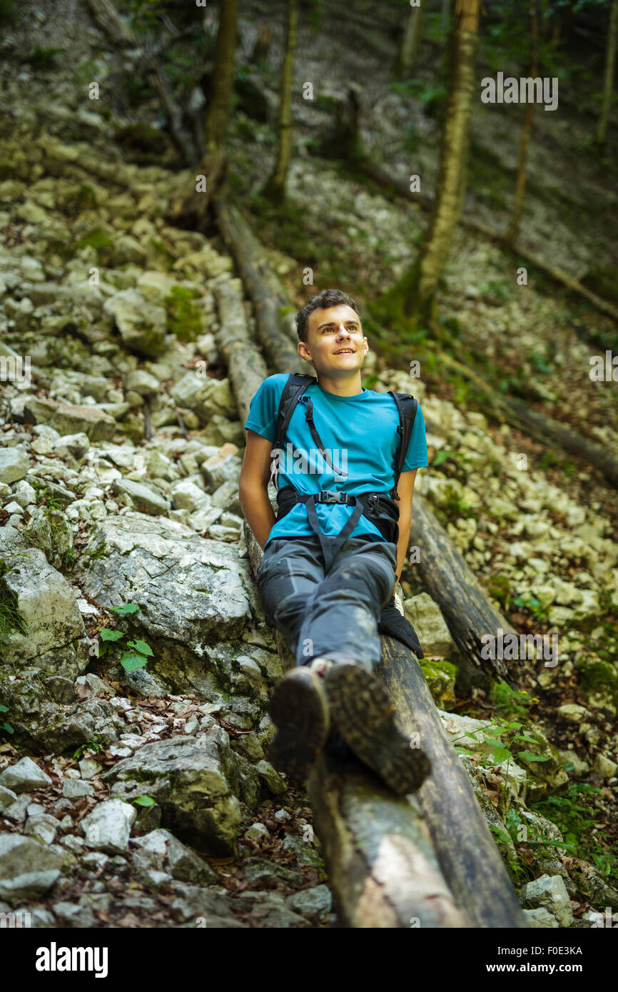 Happy teenager sitting on a log, resting after hiking on a