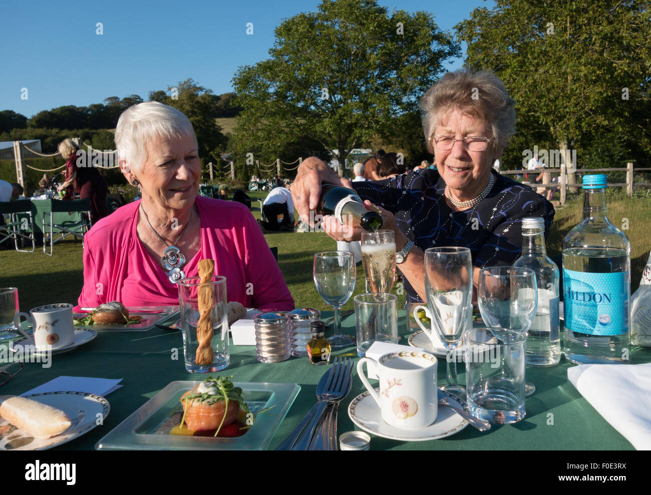 Two senior elderly women having fun with a champagne picnic, Glyndebourne, Sussex England UK - Stock Image