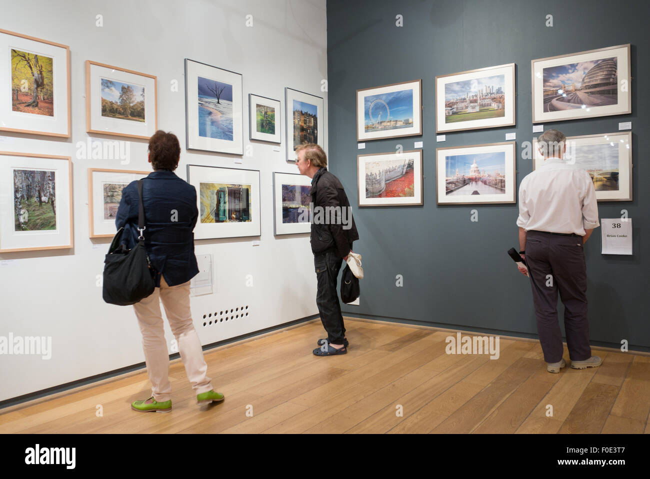 People in a gallery looking at a photography exhibition, the Mall galleries, the Mall, London UK - Stock Image