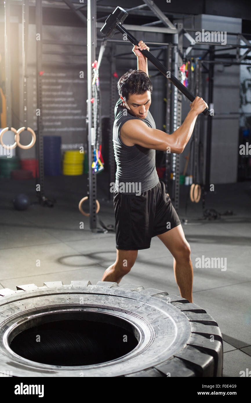 Young man hammering large tire at gym - Stock Image