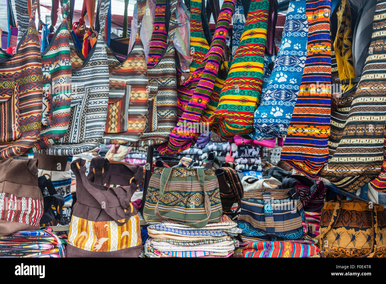 Colorful bags hanging at souvenier shop in Otavalo, Ecuador - Stock Image