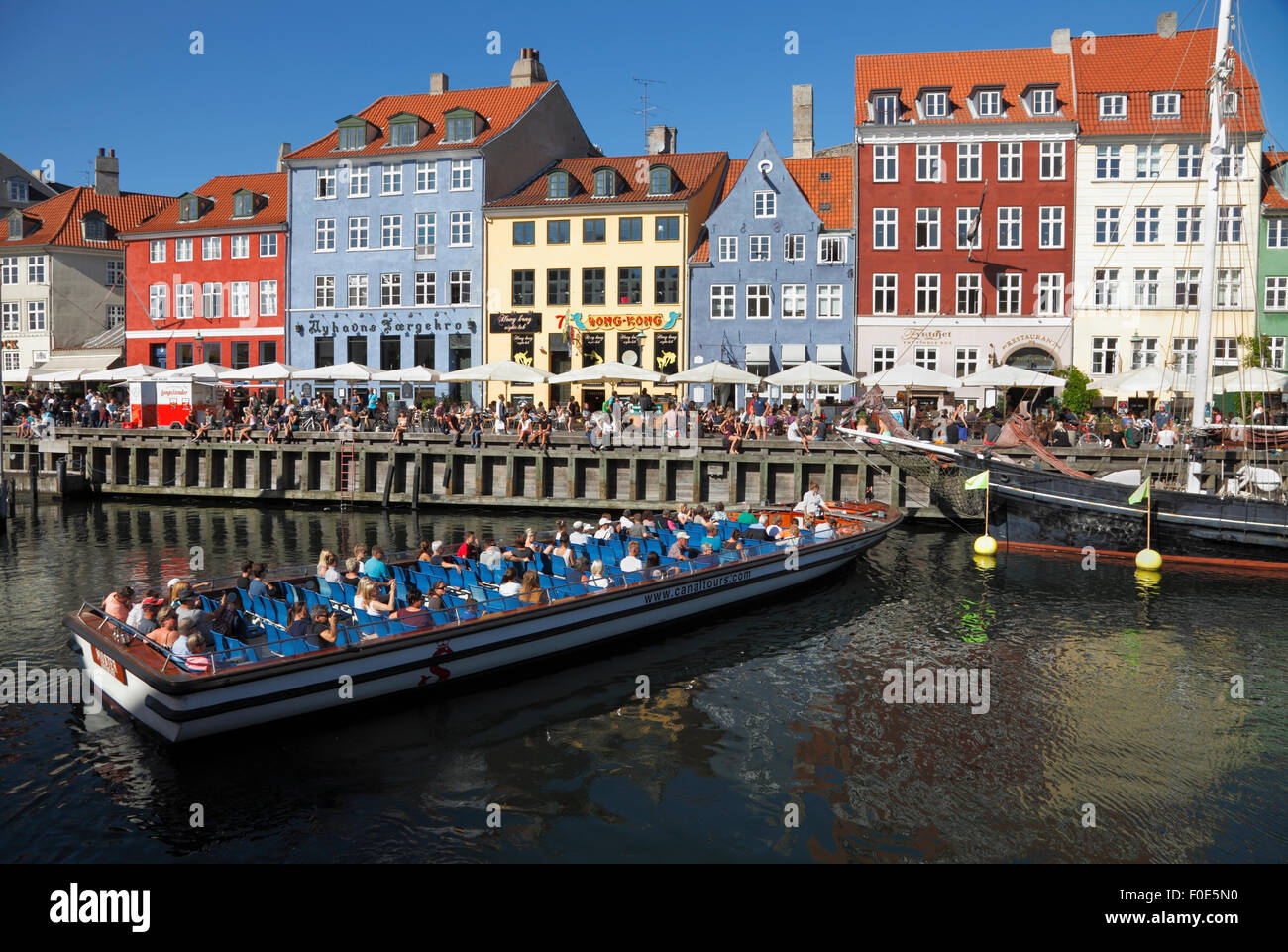 Canal tour boat turning around in crowded Nyhavn canal on a warm and sunny summer day full of tourists and visitors. - Stock Image