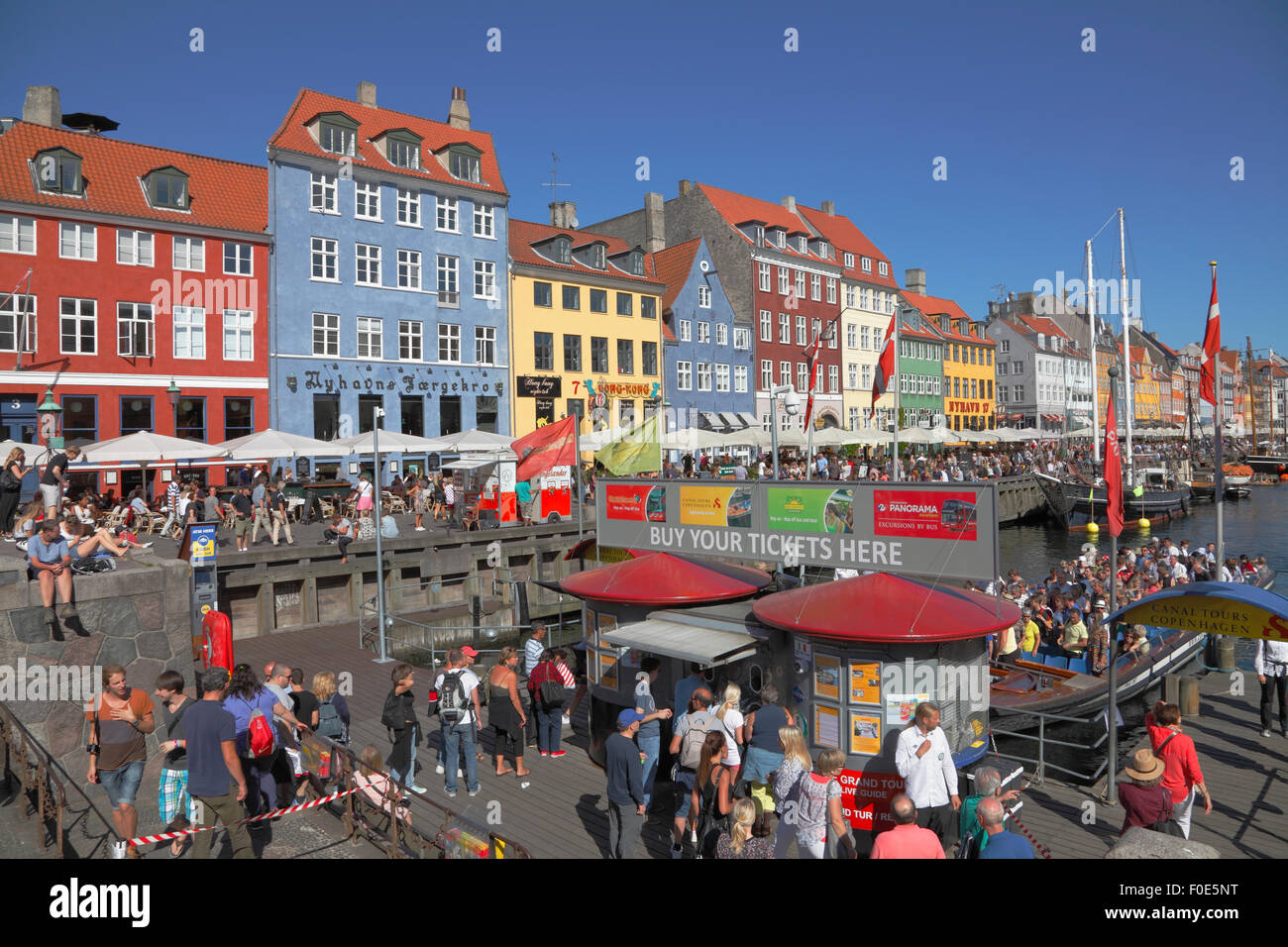 Nyhavn full of crowded canal tour boats and people at the waterside and pavement restaurants on a very est, smf - Stock Image