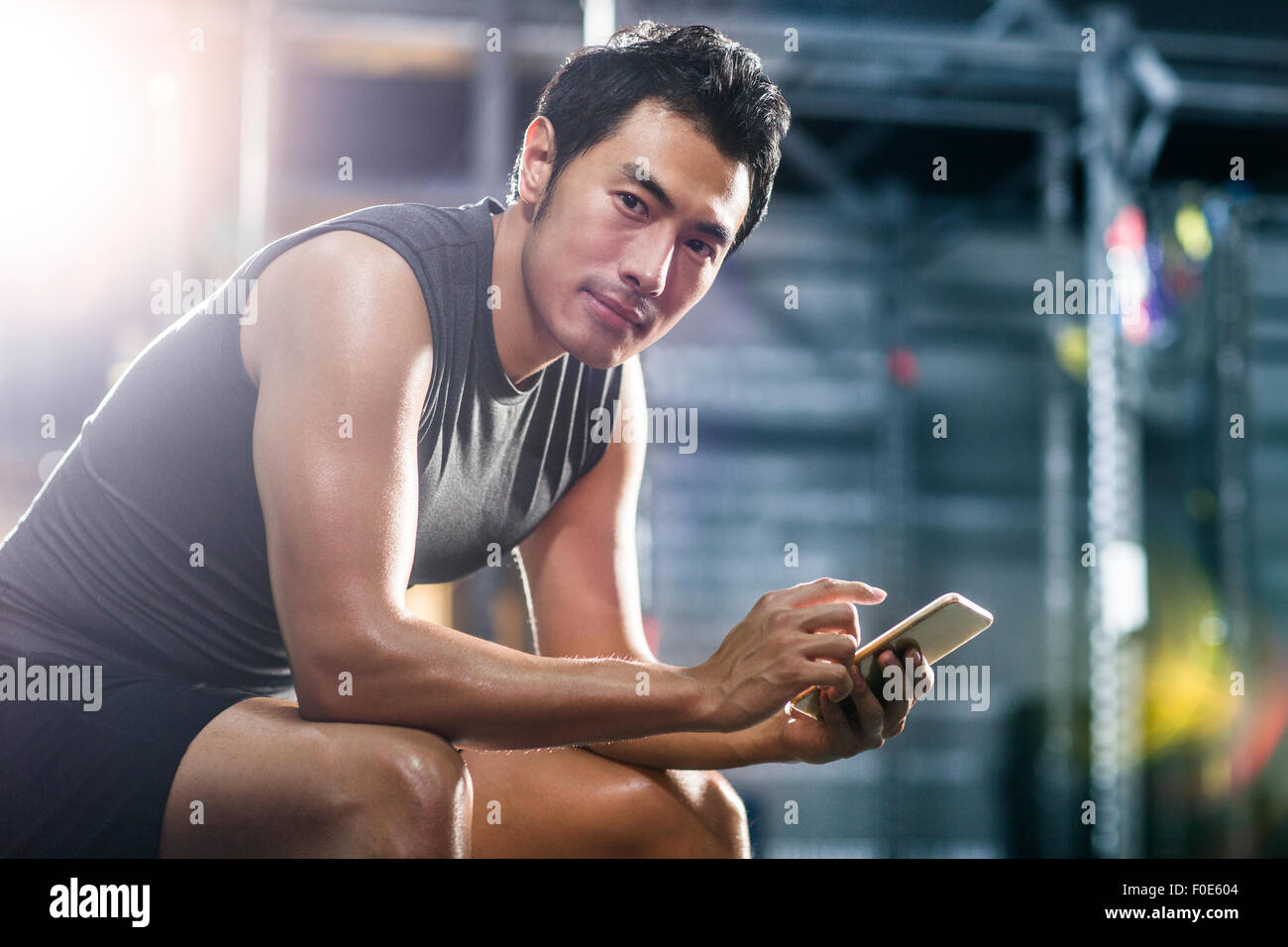Young man using smart phone in gym Stock Photo