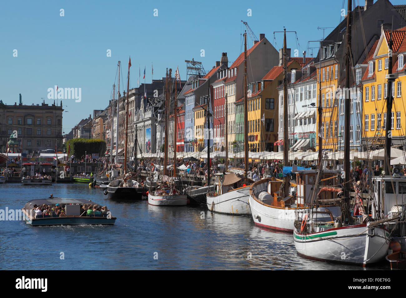 Nyhavn full of old ships, crowded canal tour boats and people at waterside and pavement restaurants on a very busy - Stock Image