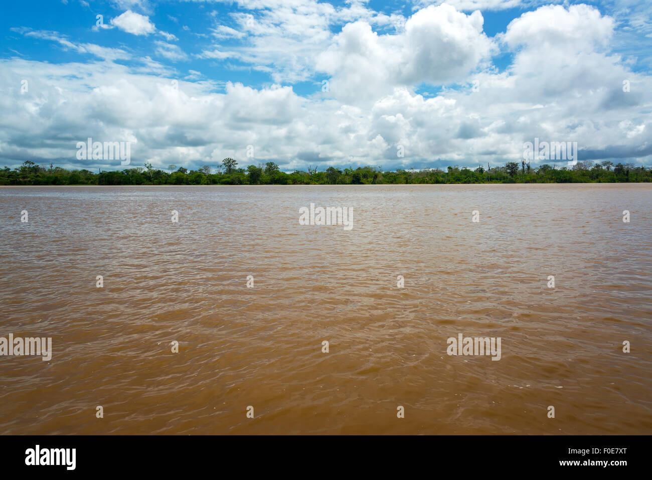 View of the wide muddy Amazon River as it slowly passes through Peru - Stock Image
