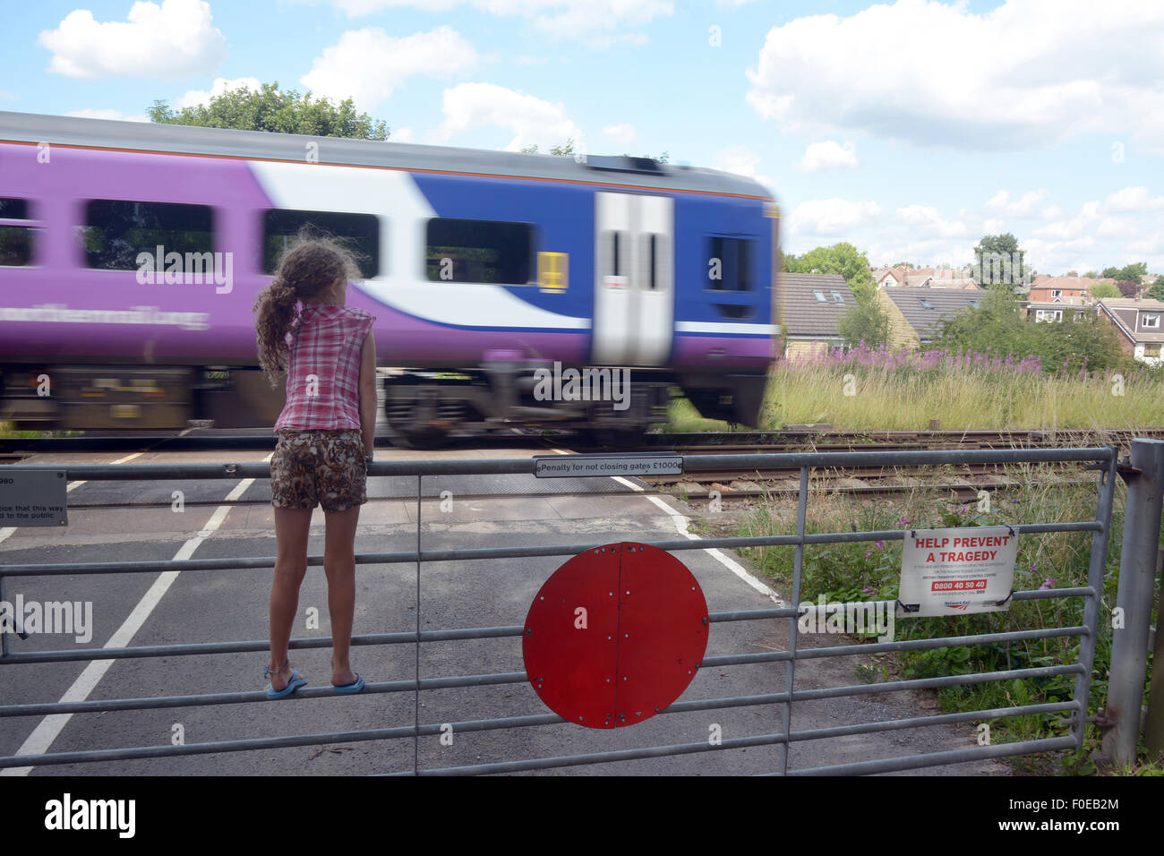 A young girl climbs on a gate at a level crossing to watch the trains go past - Stock Image