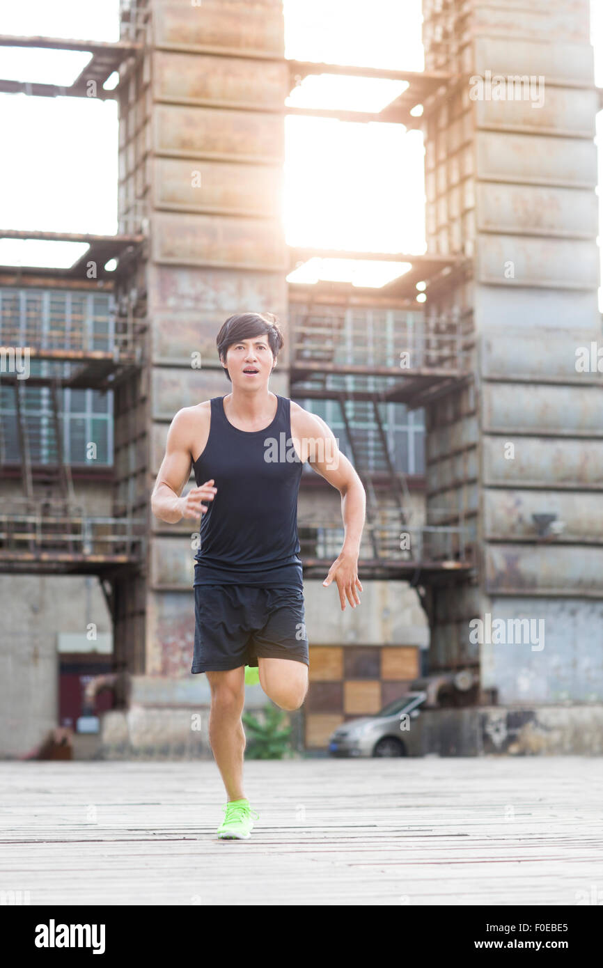 Young jogger running outdoors - Stock Image