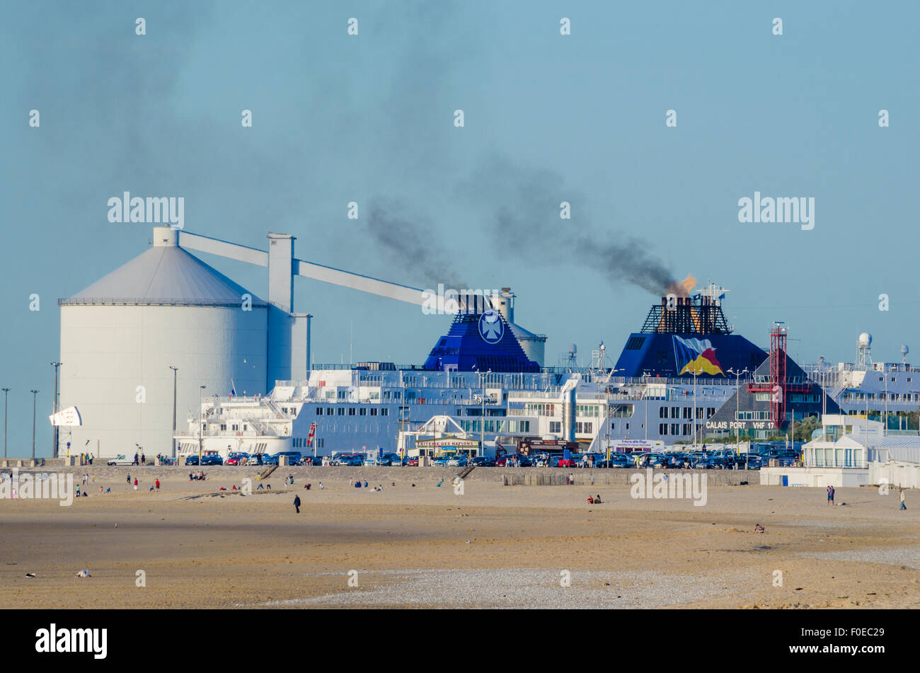 Calais harbour with channel ferries with the beach in the foreground. - Stock Image