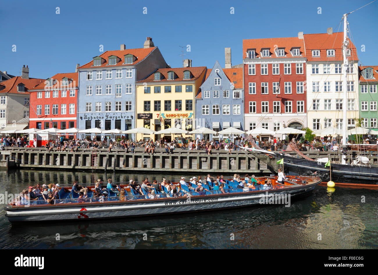 Canal tour boat turning around in crowded Nyhavn on a warm and sunny summer day full of tourists and visitors also Stock Photo