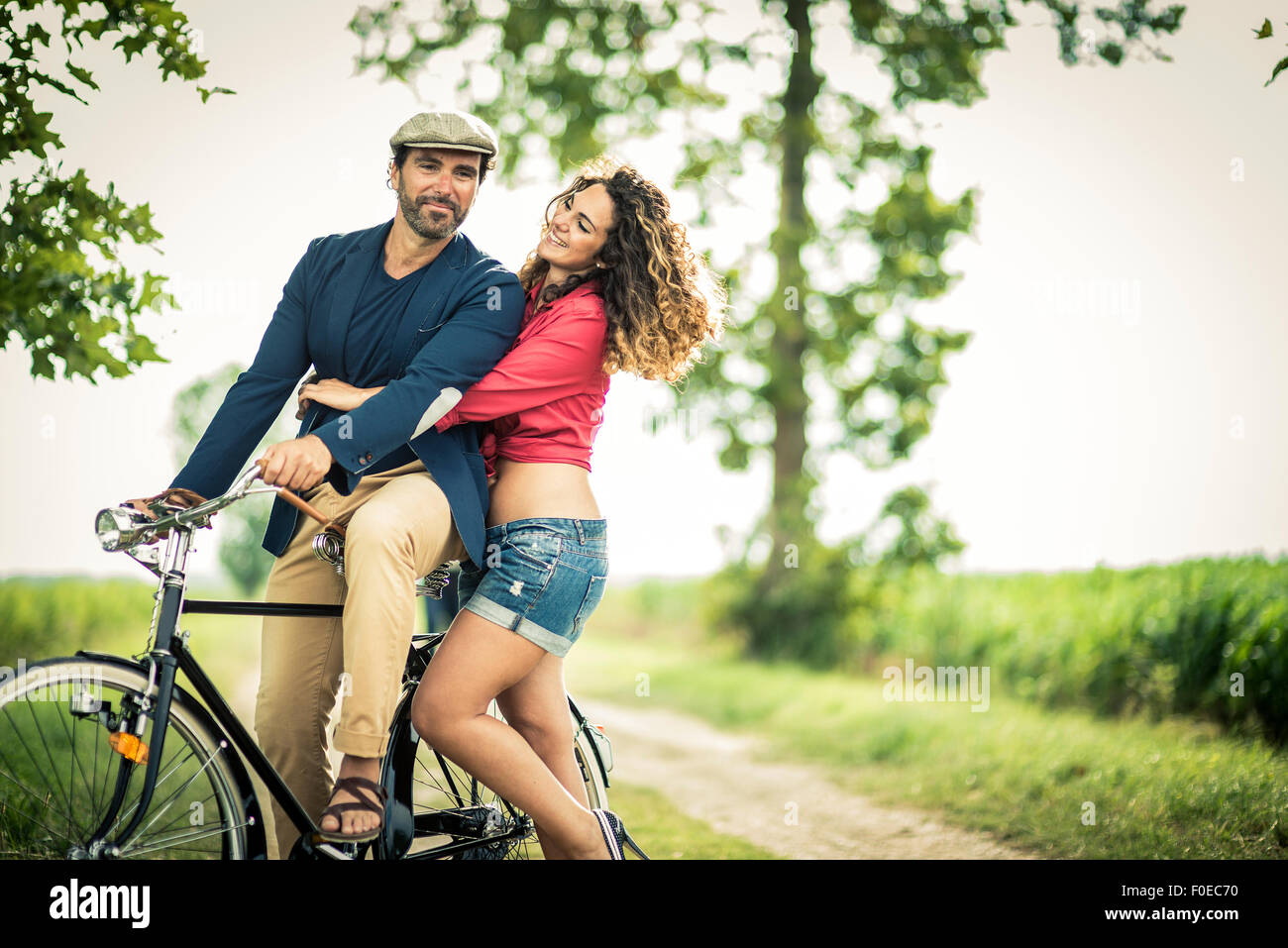 Happy couple having fun while biking on a country road - Stock Image