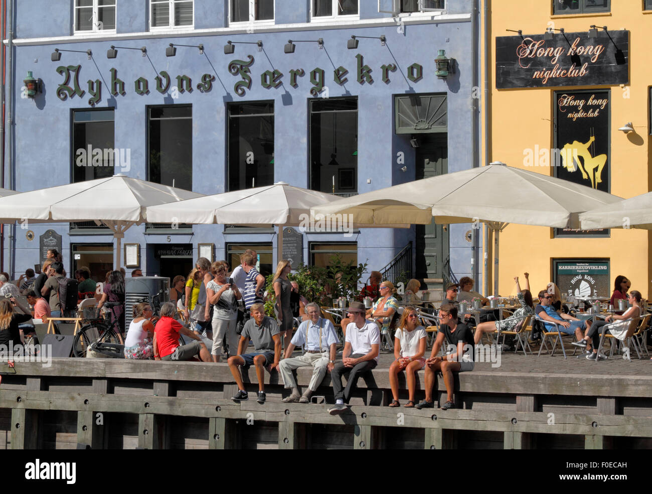 People meet and talk over a drink in the sun in the cosy ambience in charming Nyhavn. Many prefer to sit on the - Stock Image