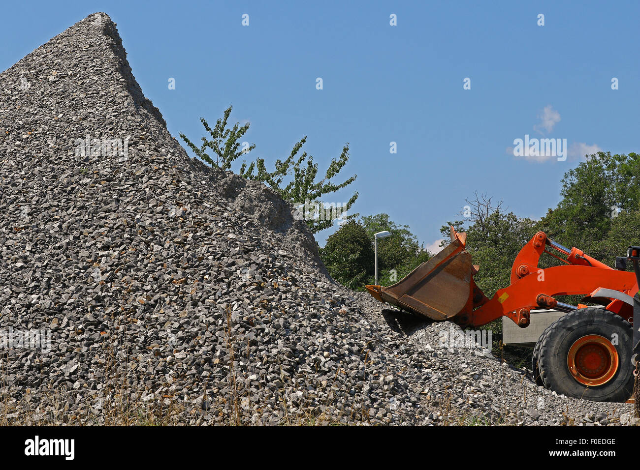 Excavator in front of a pile of rubble outside a mine against blue skies - Stock Image