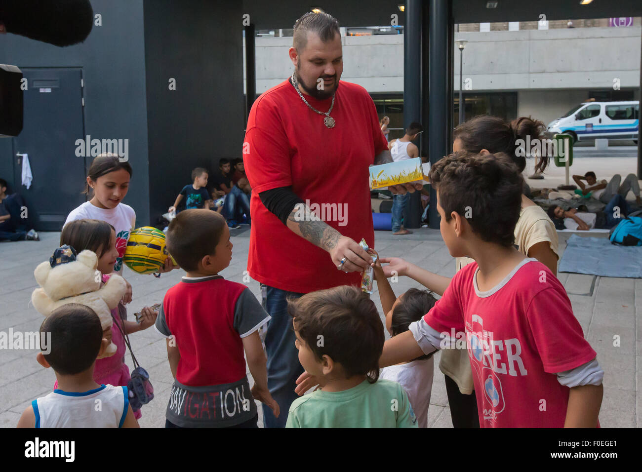(150814) -- BUDAPEST, Aug. 14, 2015 (Xinhua) -- A migration aid volunteer distributes food to illegal migrants in - Stock Image