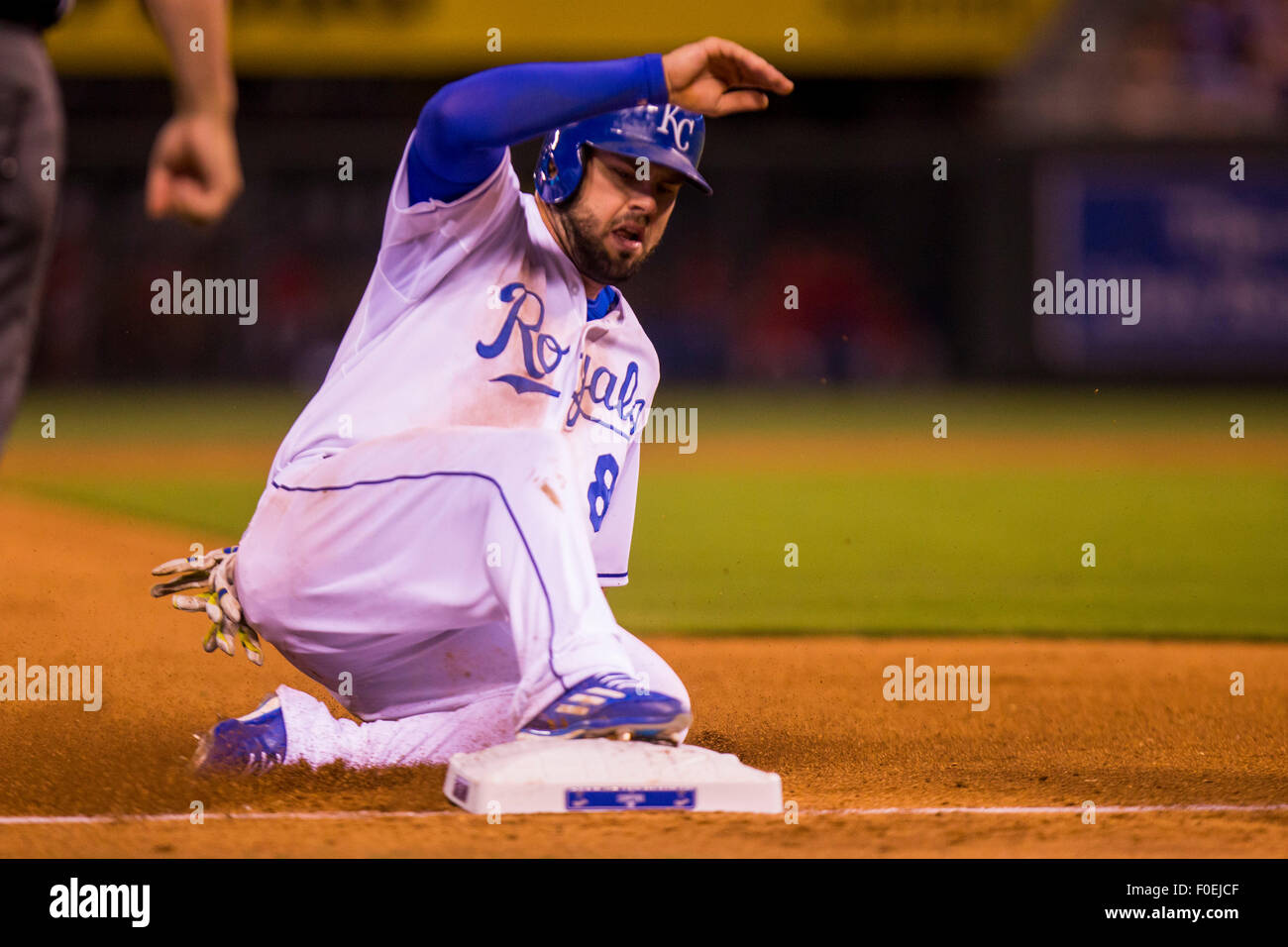 Kansas City, Missouri, USA. 13th Aug, 2015. Mike Moustakas #8 of the Kansas City Royals slides safely into third during the MLB game between the Los Angeles Angels and the Kansas City Royals at Kauffman Stadium in Kansas City MO Credit:  Cal Sport Media/Alamy Live News Stock Photo