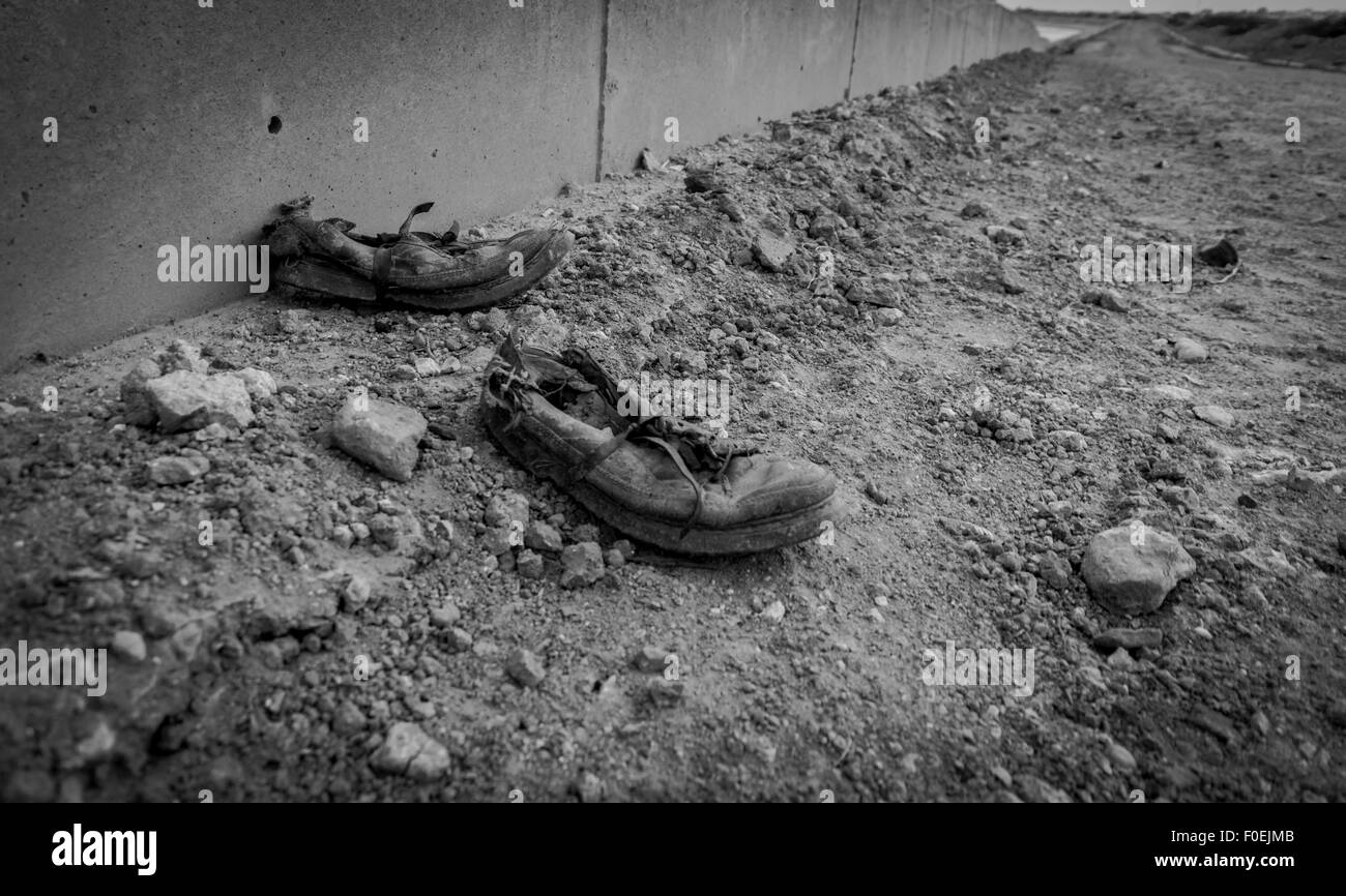 Worn out shoes against wall suggesting end of life journey - Stock Image